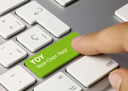 YOY Year-Over-Year Written on Green Key of Metallic Keyboard. Finger pressing key. Stok Fotoğraf