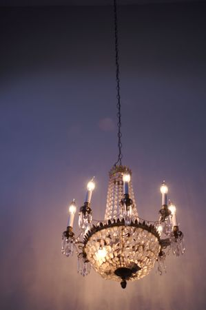 Chandelier or decorative crystal ceiling light shining on dark background  photo