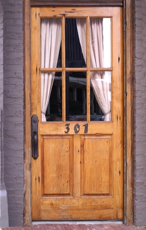 architectural exterior: Doorway with Door in Curtains in Window