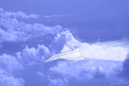 Paper airplane speeding through cloudy blue sky photo