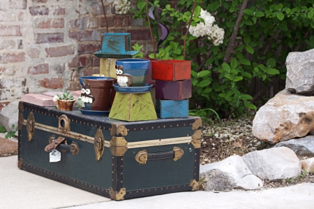 Flower pots and other items displayed on an old trunk outside a shop photo