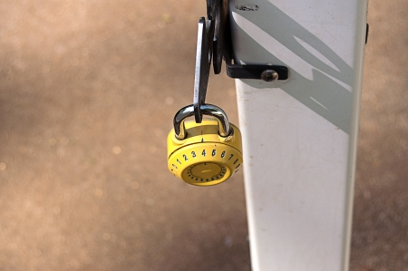 Yellow combination lock on an open garden gate photo