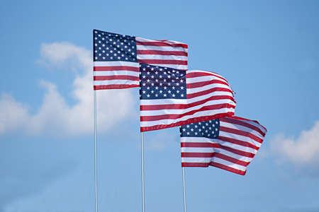 Three american flags waving in cloudy blue sky Foto de archivo