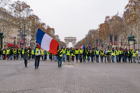 5th Yellow Vests demonstration (Gilets Jaunes) protesters against fuel tax, government, and French President Macron with French flag at Champs-Élysées