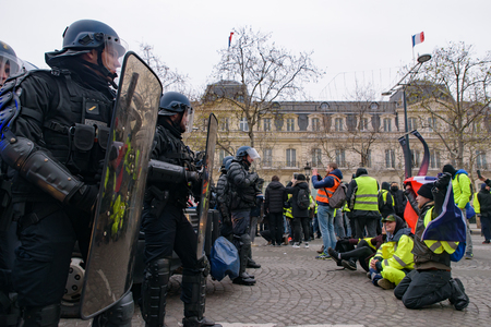 Riot police and Yellow Vests demonstration (Gilets Jaunes) protesters against fuel tax, government, and French President Macron at Champs-Élysées