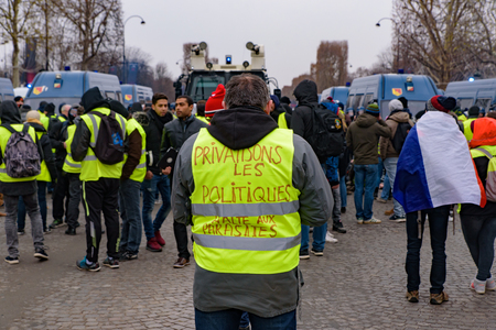 5th Yellow Vests demonstration (Gilets Jaunes) protesters against fuel tax, government, and French President Macron at Champs-Élysées with slogan on back