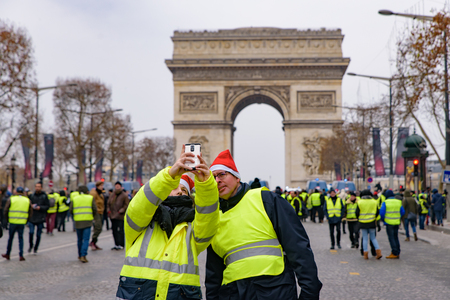 Protesters of 5th Yellow Vests demonstration (Gilets Jaunes) against fuel tax, government, and French President Macron taking selfie at Champs-Élysées
