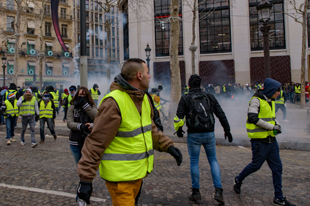 Riot police firing tear gas at Yellow Vests demonstration (Gilets Jaunes) protesters against fuel tax, government, and French President Macron at Champs-Élysées