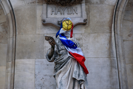 Protesters of Yellow Vests demonstration (Gilets Jaunes) against fuel tax, government, and French President Macron put yellow vest and flag on Paris Opera Garnier