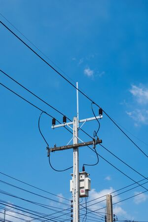 electricity posts,in to the sky,chaotic wire with nest on pole and blue sky background ,USA.