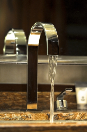 stainless steel water tap with water goes out Stock Photo