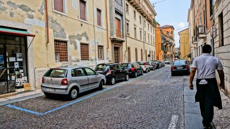 Een van de binnenstad straat in het centrum van Verona, Italië, auto's en motorfietsen parkeren in een rij.