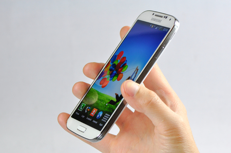 Young man is holding the newest Samsung mobile phone Galaxy S4, showing the front view.
