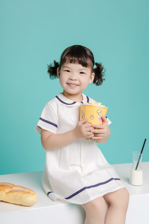 Little pretty Asian girl laughing portrait with milk and bread, healthy and happy lifestyle.