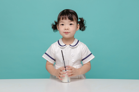 Little pretty Asian girl laughing portrait with milk, healthy and happy lifestyle.