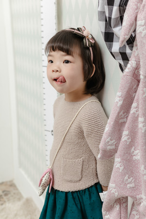 Little pretty Asian girl standing in a normal indoor background. Stock Photo