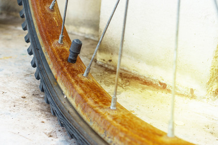 Close up the rust bicycle wheel and flat tyre, vintage retro style bicycle. election Focus on Tyre Valve Stem.
