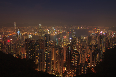 tilt: Evening aerial view panorama of Hong Kong skyline and Victoria Harbor. Travel destinations.