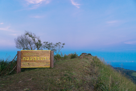 PHAYAO - THAILAND - NOVEMBER 22 2016 - The Sign of Peak of Doi Phu Lang Kha(Doi meaning is Highest peak) with blue and red sky background biên tập
