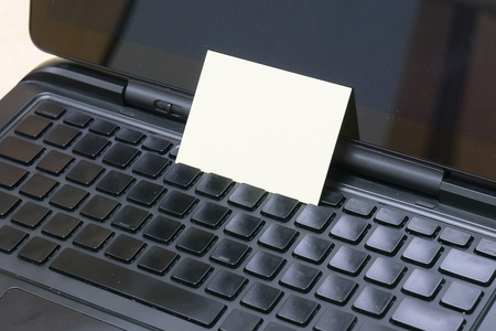 Yellow Sticky note put on the keyboard for notice or remind memory.