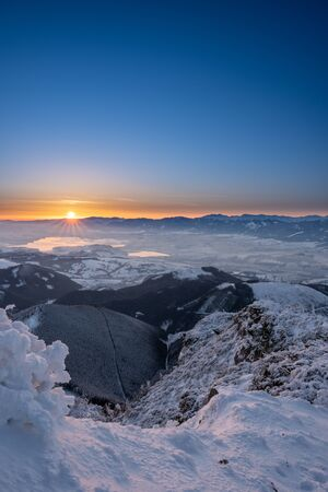 snow covered landscape sunrise from Velky Choc mountain in winter, with view of low and high Tatras and Liptovska Mara, slovakia ,portrait photo