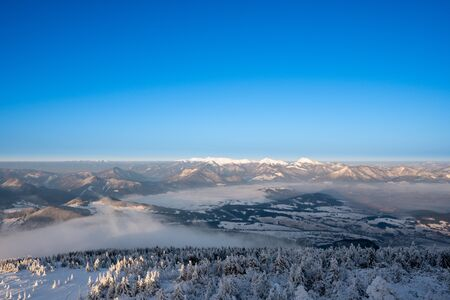 winter landscape in mountains illuminated at sunrise with fog in valley and beautiful snowy trees, slovakia Velky Choc