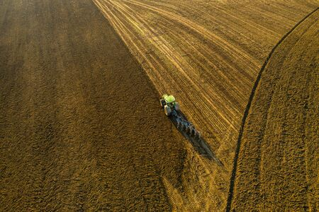 aerial shot of tractor during plowing field in autumn at sunset