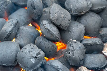 Top View Of Hot Flaming Charcoal Briquettes Glowing In The BBQ Grill Pit. Abstract Red Black Background, Texture Or Wallpaper. Burning Coals For Cooking Barbecue Food. Close Up. Stock Photo