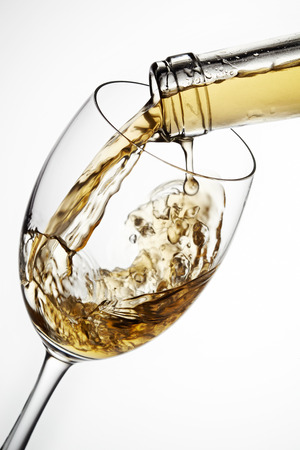 pouring wine: Glass of wine with splash, isolated on white background