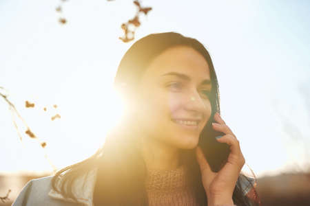 Close up portrait of a smiling young female holding her smartphone near ear outdoors in a warm autumn evening
