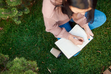 Top view of calm and concentrated female student planning her day in a paper notepad on a green grass lawn outside 写真素材