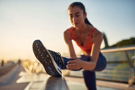 Fit girl is stretching outdoor. Slim beautiful woman workout. Jogging in the city at sunrise. Close up photo of stretching