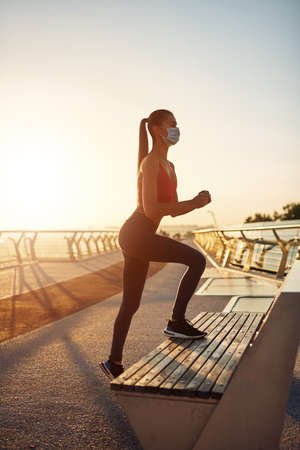 Beautiful young girl workout at sunrise. Exercises for the buttocks. Step platform for outdoor training. Sport in the city Standard-Bild - 151364564