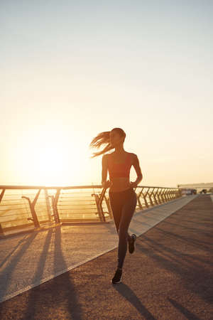 Beautiful girl is running. Woman healthy lifestyle outdoor. Exercise in fresh air. Jogging in the city at the bridge at sunrise. Glare of sunlight. Standard-Bild