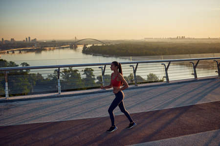 Young Woman is running. Healthy lifestyle outdoor. Girl jogging at the bridge at sunrise. Beautiful Kyiv city view with skyline.