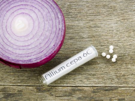 Allium cepa homeopathic medicine on a rustic wooden table with a red onion. Allium cepa is made of red onion. Stock Photo