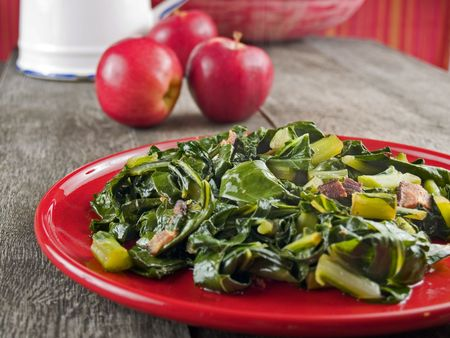 greens: Collard greens and bacon on a red plate with apples and a water pitcher in the background.