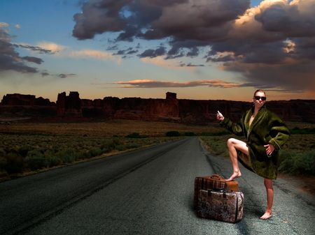 Woman hitchhiking barefoot dressed in fake fur coat photo