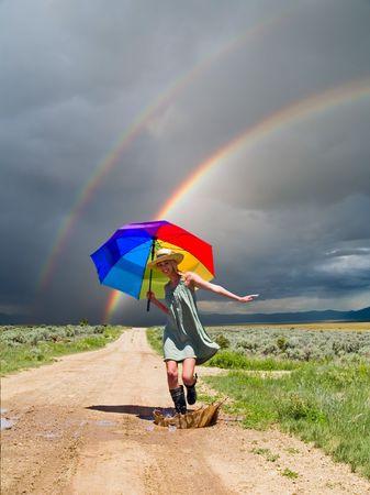 lluvia paraguas: Chica salpicadura de agua en un charco despu�s de una lluvia Foto de archivo
