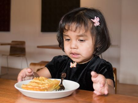 native american baby: Little Native American girl eating a slice of quiche in a coffee shop