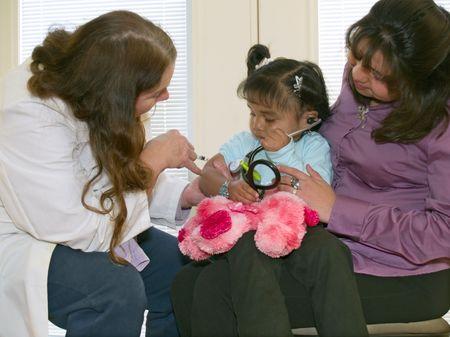 medico pediatra: Pediatra inocular a una peque�a ni�a amerindia que est� escuchando a coraz�n de un cachorro de juguete con un estetoscopio.