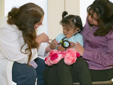 vaccinating: Pediatrician inoculating a little Native American girl who is listening to a toy puppys heart with a stethoscope. Stock Photo