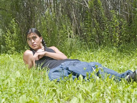 modern: Modern day Native American 15 year old teenage boy relaxing on lawn