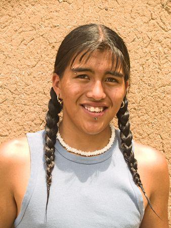Retrato de un apuesto muchacho amerindio 15 año de edad por un muro de adobe Foto de archivo