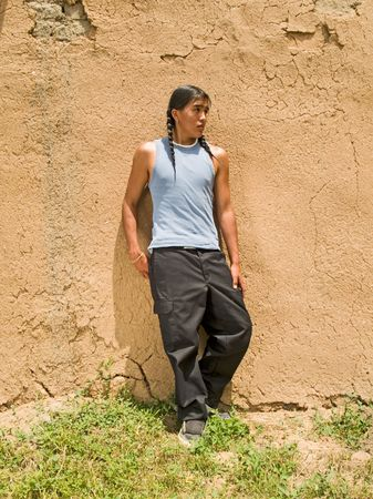 indio americano: Apuesto muchacho de 15 a�o de edad amerindio por un muro de adobe Foto de archivo