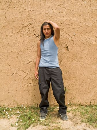 Handsome 15 year old Native American boy by an adobe wall