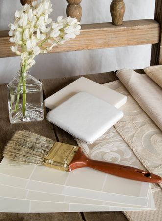 White color cards, fabric swatches and tiles on an old, rustic, unpainted chair with a paintbrush and white flowers. Stock Photo - 5812779