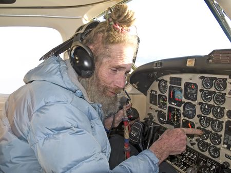 Strange older pilot with a feather in his dreadlocks reading the instruments photo