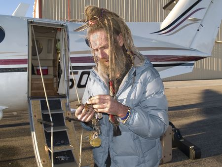 Eccentric older gentleman with a feather in his dreadlocks looking for a key for his aircraft photo