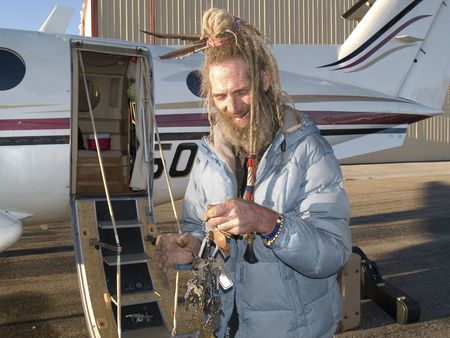 Eccentric older gentleman with feathers in his dreadlocks holding a key for his aircraft photo